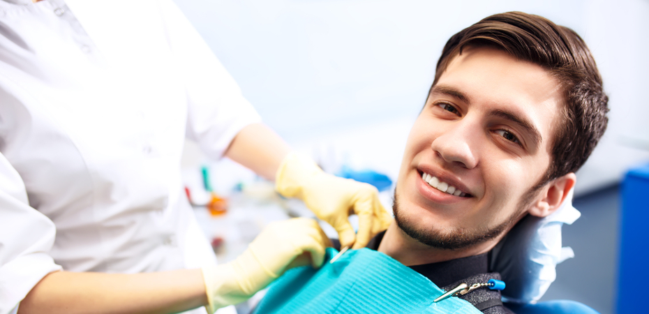 Young man sitting in dentist chair with dentist clipping on napkin