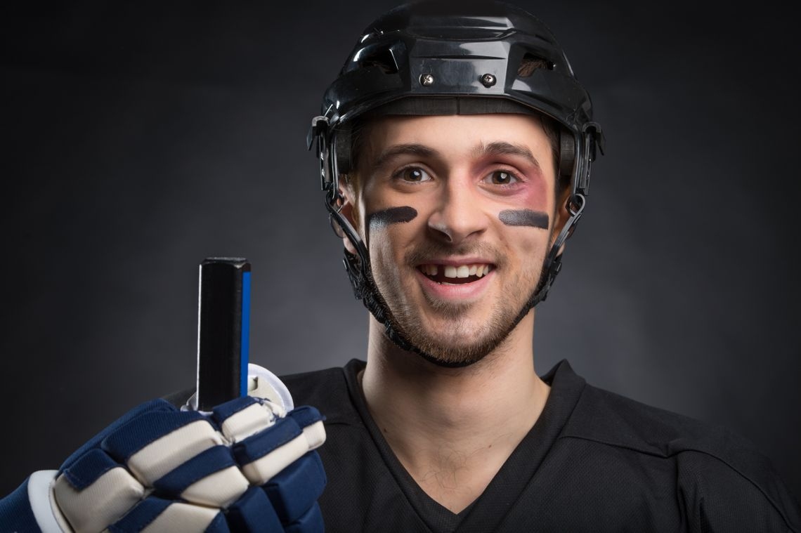 a hockey player smiling with one tooth missing