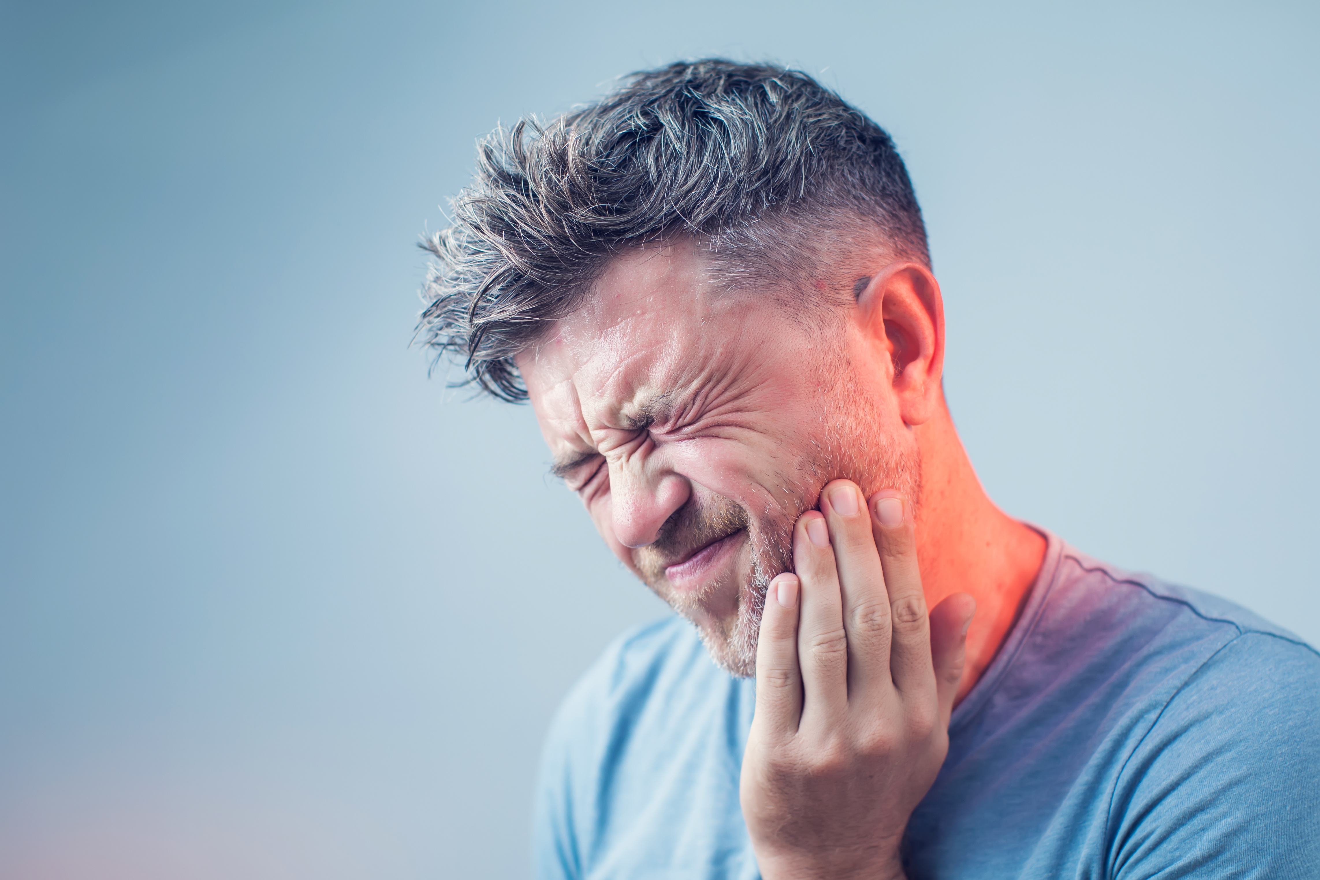man experiencing severe tooth pain requiring emergency dental assistance