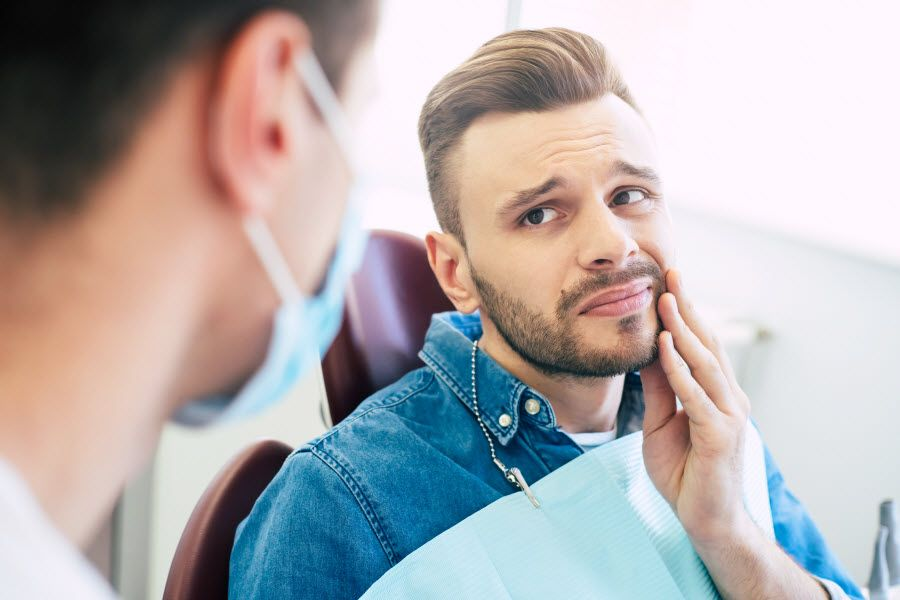 concerned patient asking dentist about gum pain and bleeding when flossing